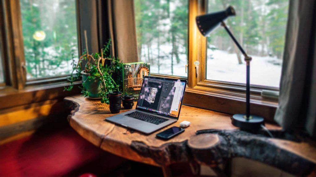 organizacja pracy w domu biurko z surowego drewna z widokiem na las