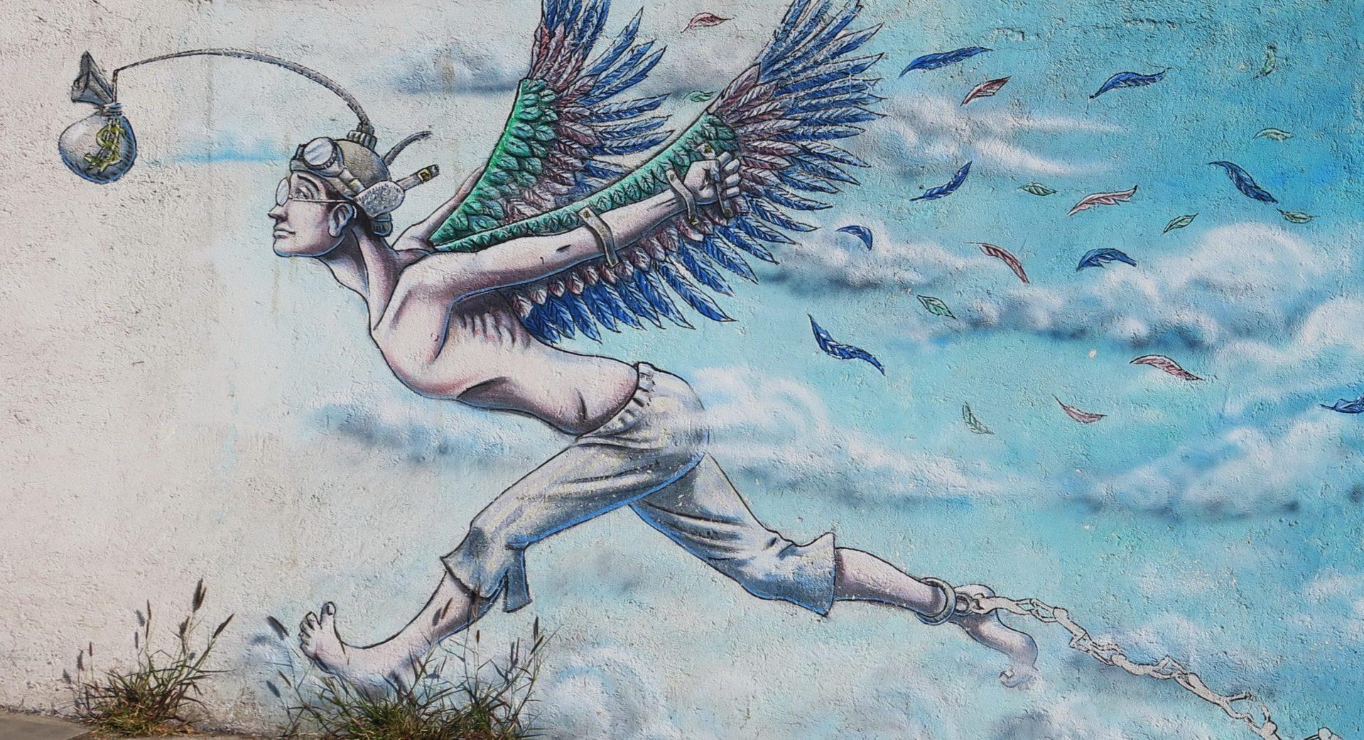 Grafika przedstawia mural, na którym młody chłopak z przywiązanymi do rąk skrzydłami biegnie za sakiewką, która wisi przed jego oczami. TO ilustracja artykułu o tym, jak freelancer odprowadza podatki.