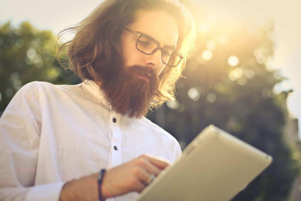 Młody mężczyzna z brodą i w okularach z czarnymi oprawkami trzyma w ręku tablet. To przykład tego, jak może pracować freelancer