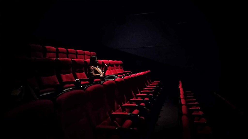 kobieta siedzi sama na widowni
