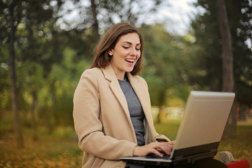 Młoda dziewczyna siedząca z komputerem w parku. Pracuje jako freelancer.