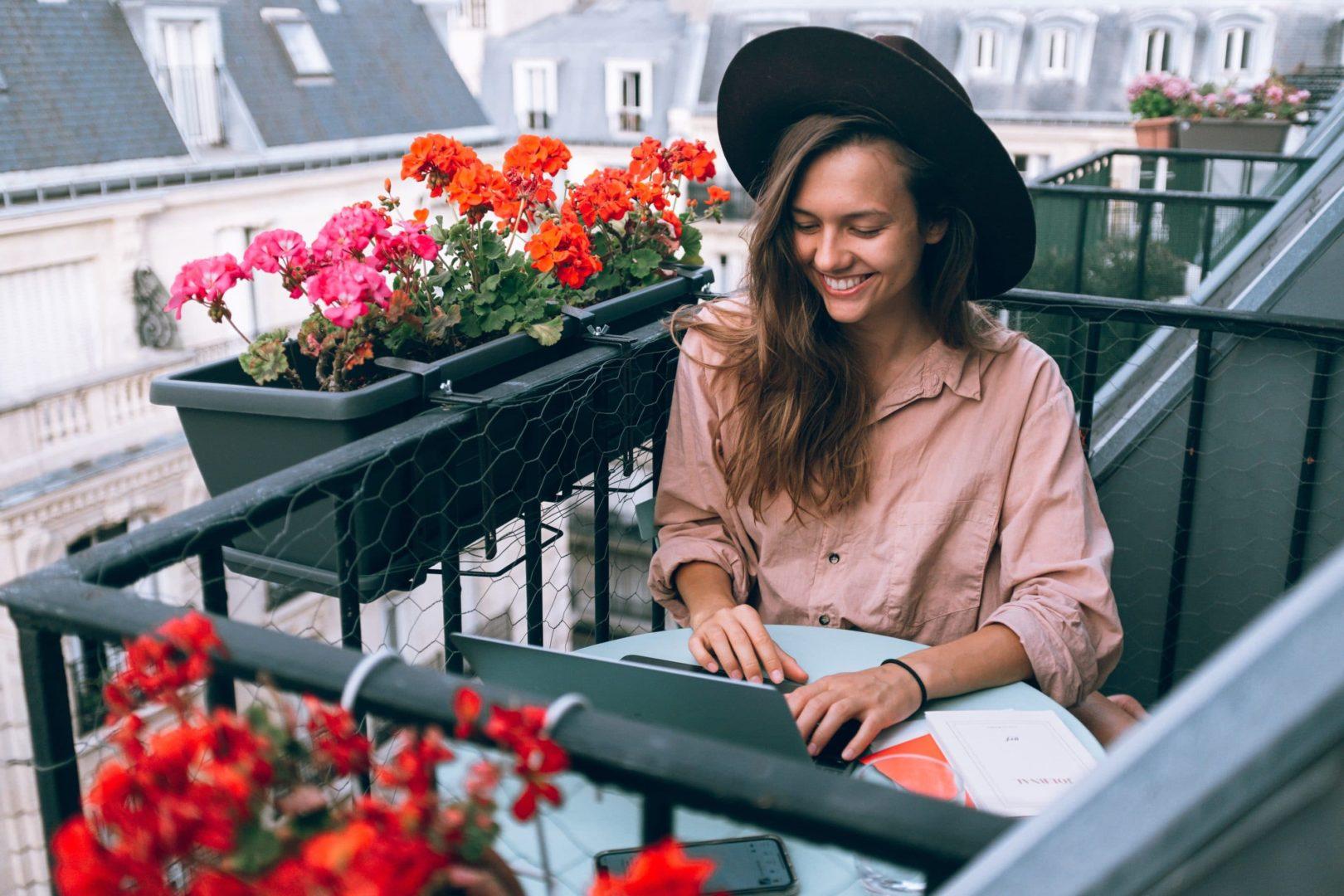 Młoda dziewczyna pracująca na komputerze z balkonu. To przykład tego, jak wygląda praca freelancera.