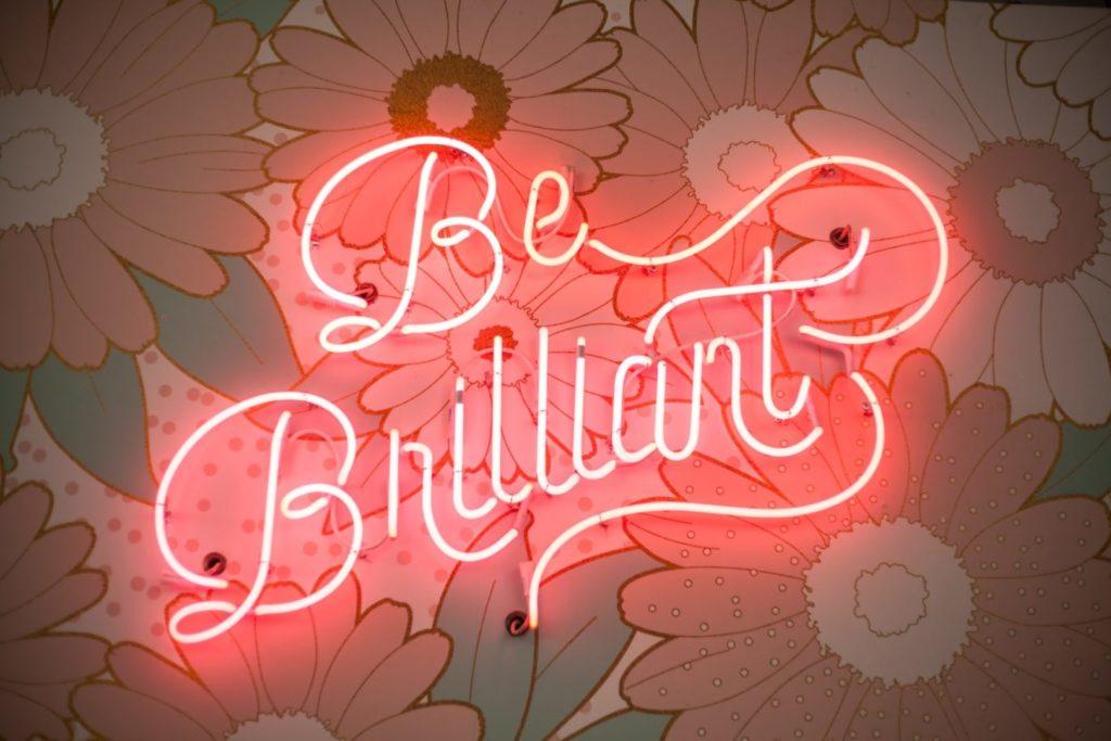 Neon z napisem: be brilliant. To przykład na skuteczny copywriting