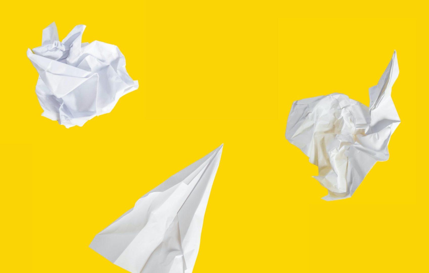Zdjęcie przedstawia zmięte w kulki dwie kartki papieru i jeden papierowy samolocik. Grafika stanowi ilustrację tekstu o tym, czym jest selfpzblishing.