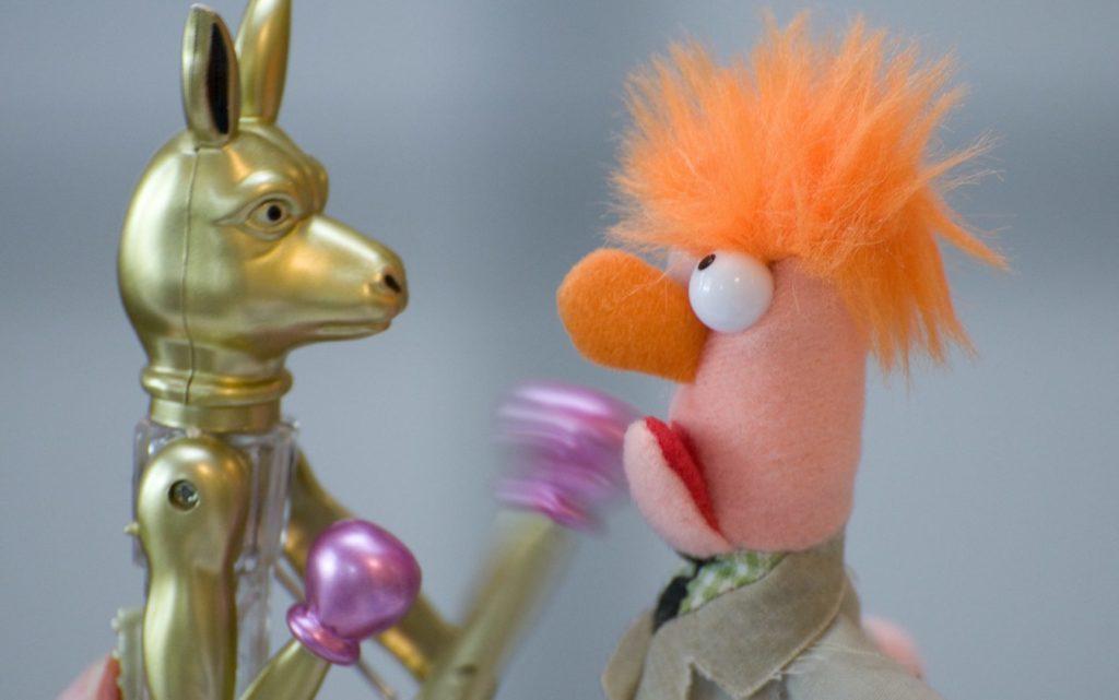 Na obrazku widać dwie zabawki kłócące się ze sobą. Jedna z nich to złoty wilk z różowymi rękawicami bokserskimi, a druga to mupet z rudą czupryną. Porozumienie bez przemocy pozwala uniknąć kłótni.