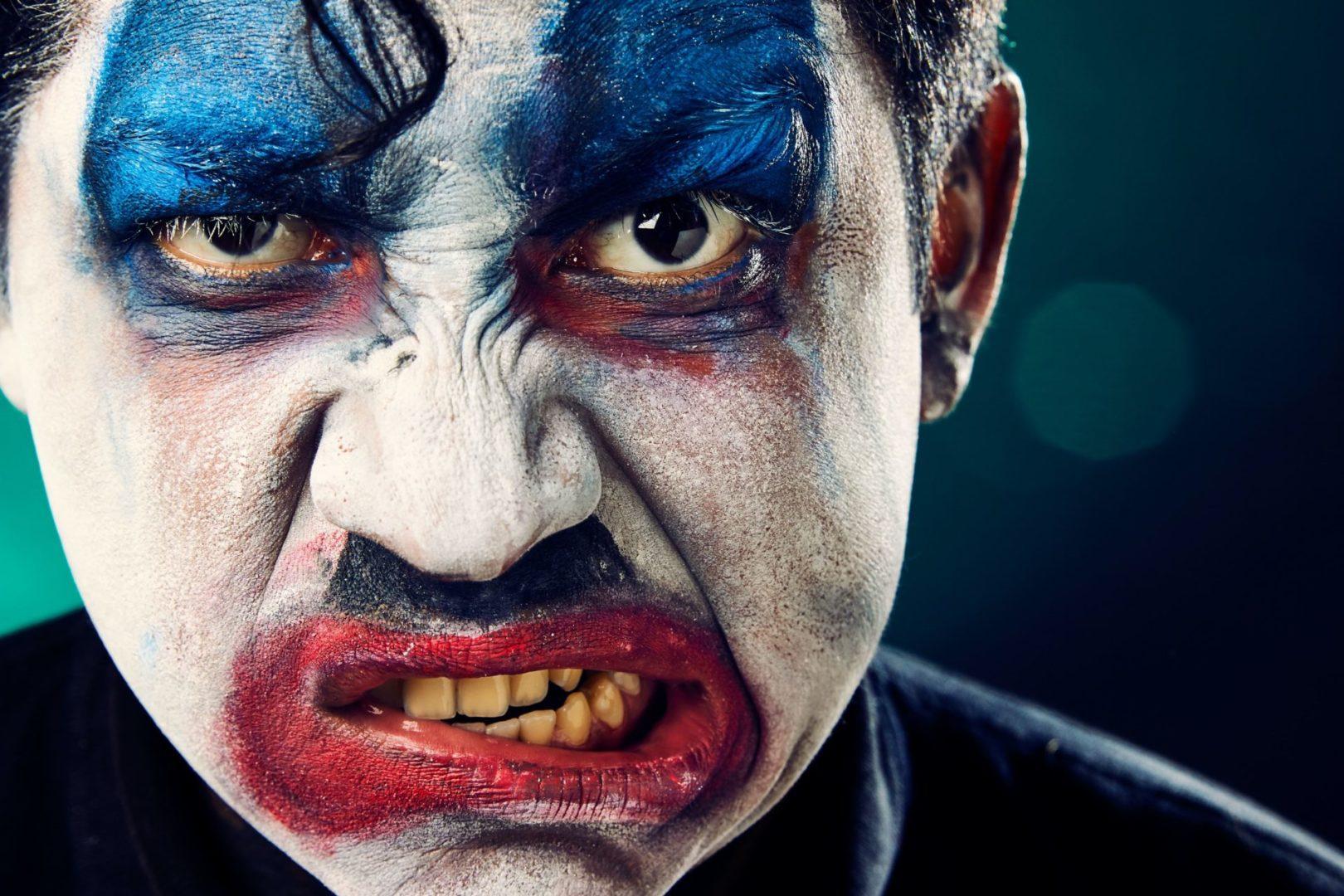 Ilustracja artykułu o porozumieniu bez przemocy. Na zdjęciu mężczyzna umalowany jak klaun, który robi minę, wykrywając usta.