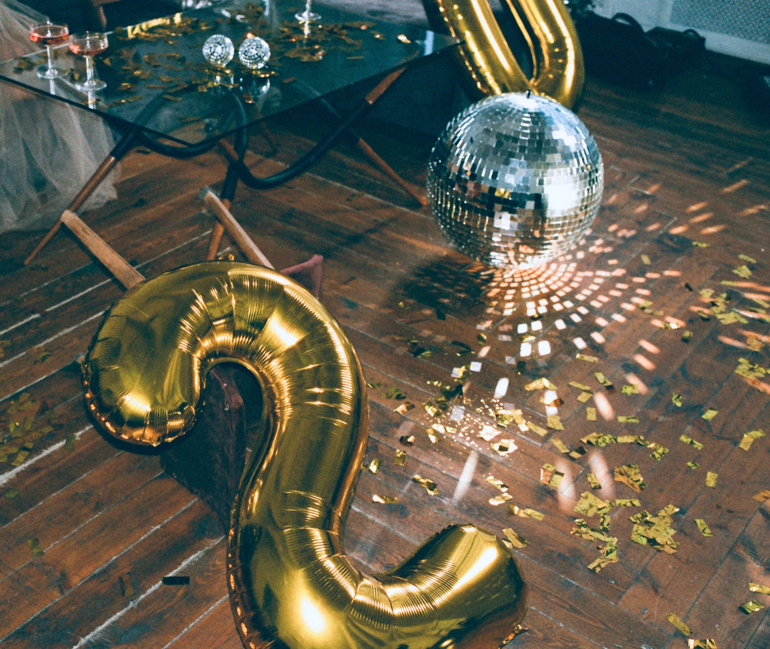 Na drewnianej podłodze leży złoty balon, a obok niego kula dyskotekowa.