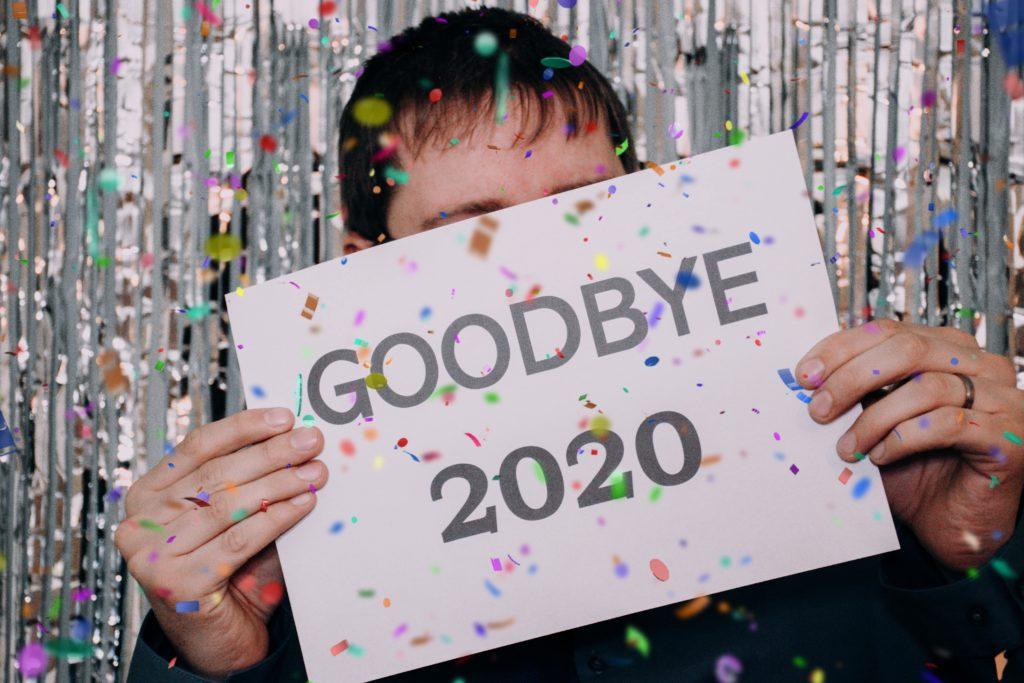 """Młody mężczyzna z krótką grzywką stoi na tle błyszczącego materiału i trzyma w dłoniach kartkę z napisem: """"Goodbye 2020""""."""