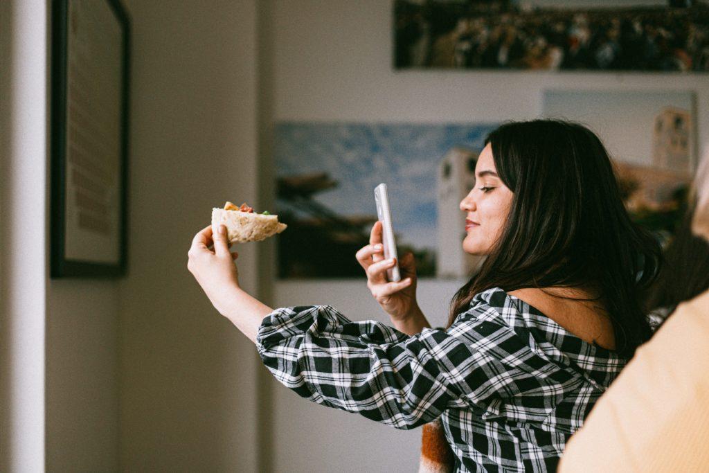 Dziewczyna robi telefonem zdjęcie trzymanemu w ręce kawałkowi pizzy.