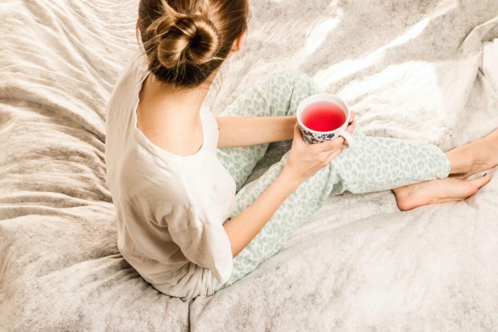 Kobieta siedzi w łóżku w piżamie, w ręku trzyma kubek owocowej herbaty.