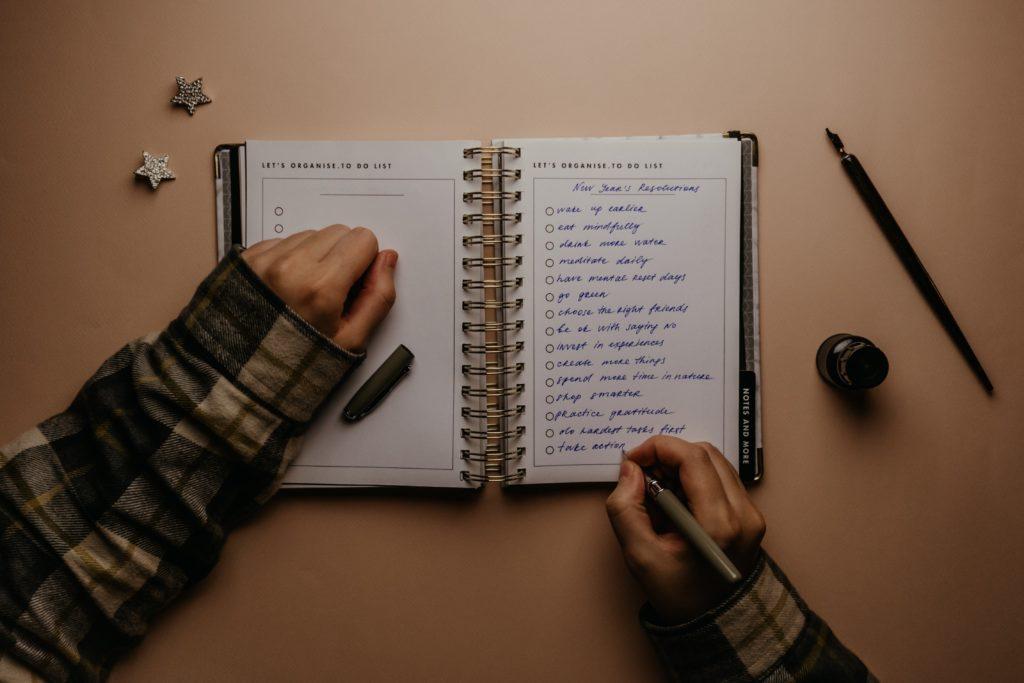 Na zdjęciu widać dłonie człowieka spisującego w organizerze noworoczne postanowienia.