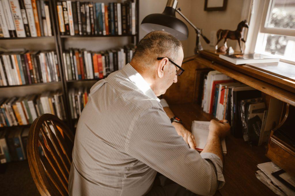 Mężczyzna w średnim wieku siedzi przy biurku i pisze w zeszycie.