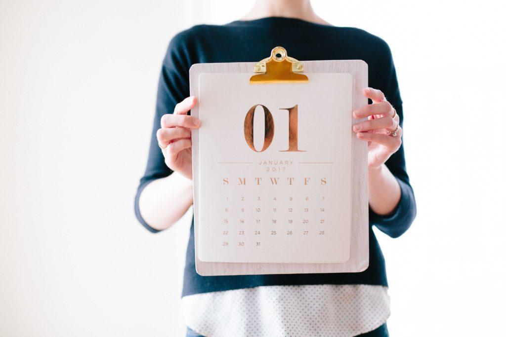 Kobieta trzymająca w dłoniach kalendarz.