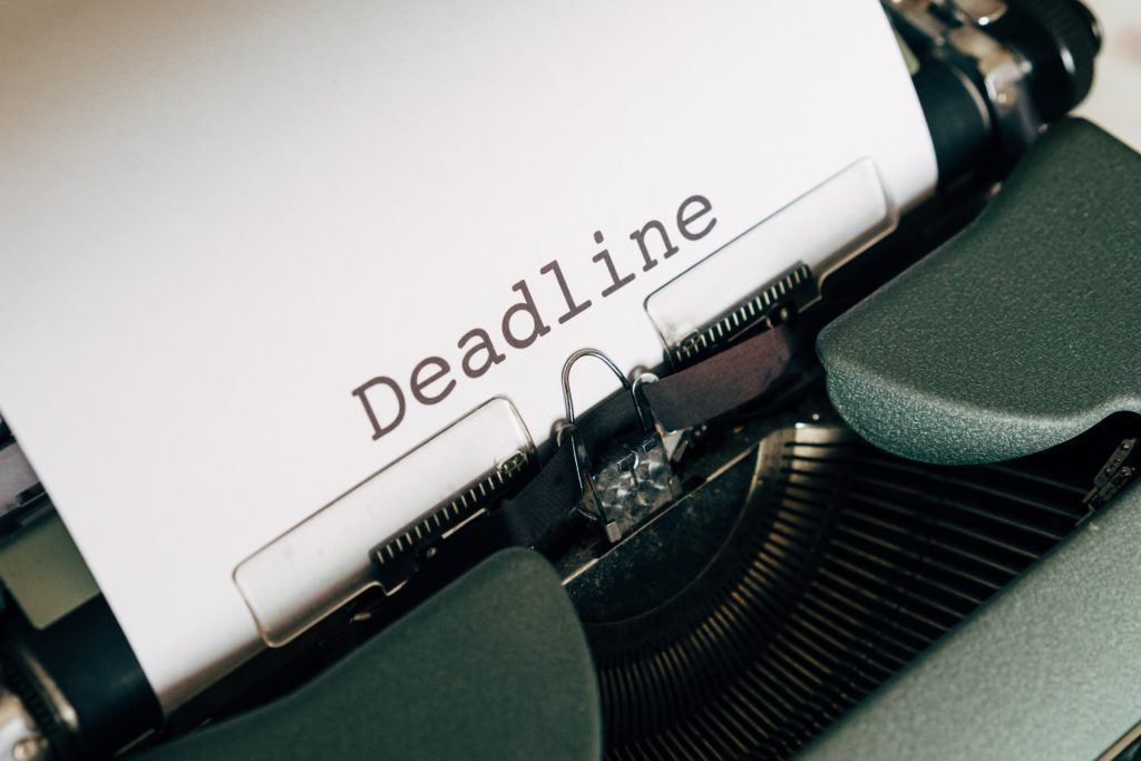 """Napis """"deadline"""" na kartce wystającej z maszyny do pisania."""
