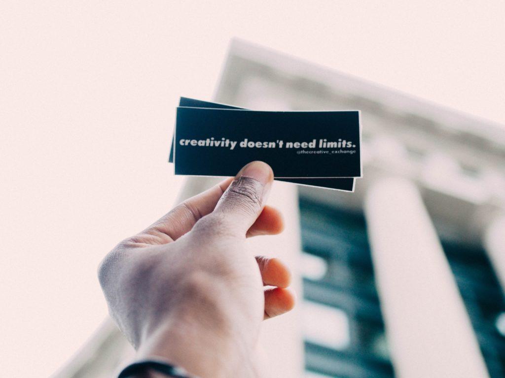 """Ręka trzymająca kartkę z napisem """"creativity doesn't need limits"""". Przedsiębiorczość wymaga bycia kreatywnym."""