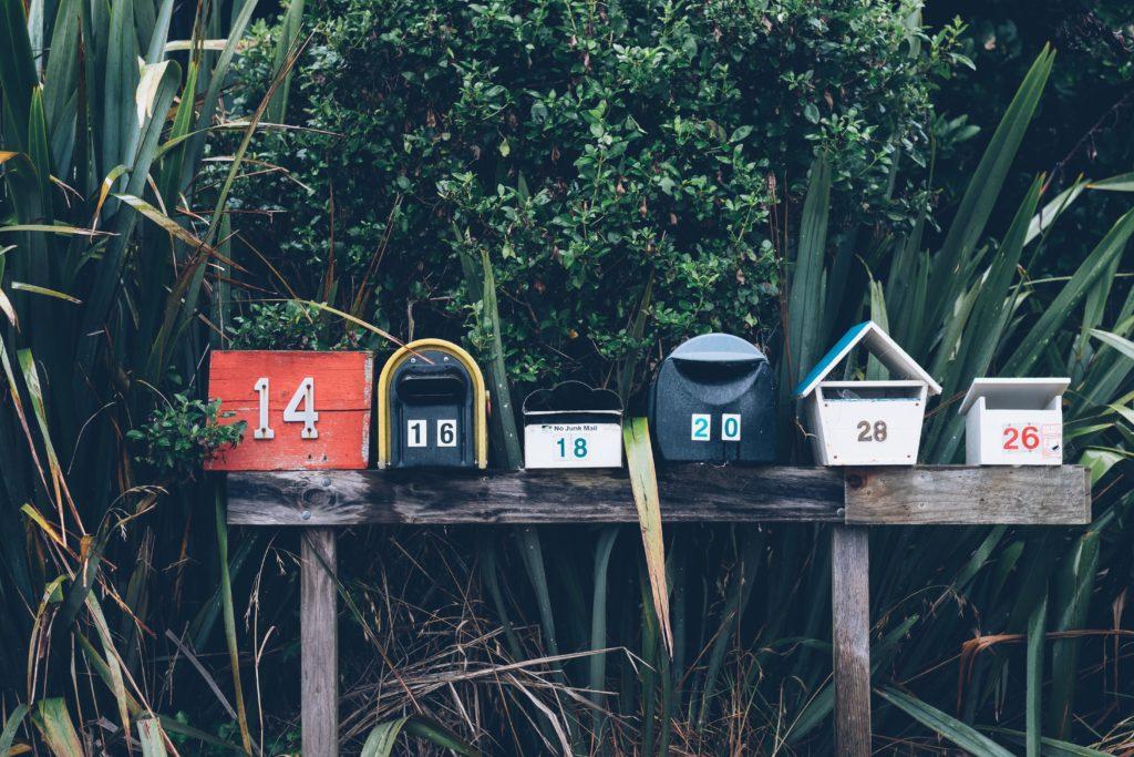 Zdjęcie przedstawia sześć skrzynek na listy w różnorodnych kształtach i kolorach, otoczonych przez bujną roślinność. Obrazek nawiązuje do narzędzi poczty tradycyjnej, która została zastąpiona przez elektroniczną i jej zdobycze - takie jak newsletter.