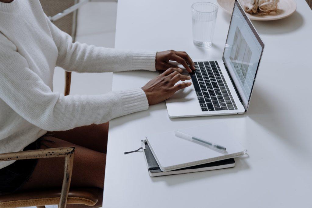 Zdjęcie przedstawia dłonie i tułów kobiety, która siedzi przy biurku i pracujące na komputerze.
