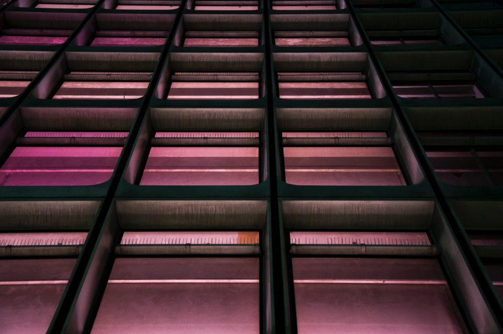 """Obraz przedstawia rząd kwadratowych, betonowych  kształtów sfotografowanych od dołu i podświetlonych na neonowy róż. Nawiązuje to do angielskiego opisu kreatywności """"thinking outside the box"""" - myślenia poza pudełkiem."""