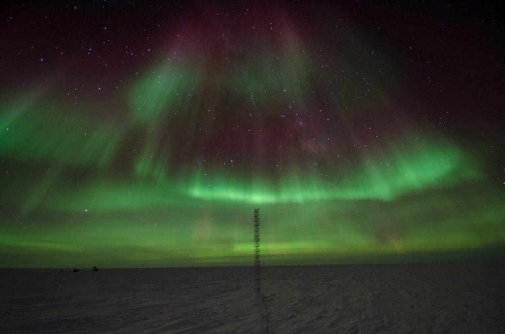 Zdjęcie zorzy polarnej. Zielona łuna zdobiąca granatowo-fioletowe, gwiaździste niebo, roztacza się nad bezludnym, śnieżnym horyzontem.