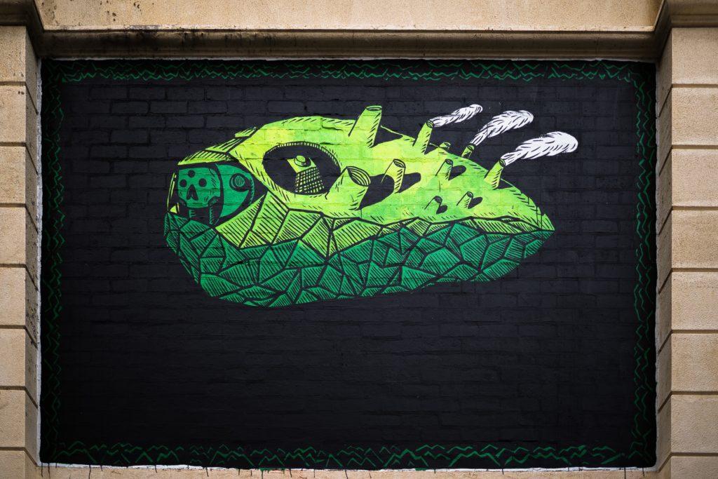 Fotografia przedstawia street art. Na   czarnym tle widnieje zielony stworek. Zbudowany jest z elementów industrialnych takich jak kominy, przyciski, elementy obudowy oraz z trójkątów. Kształt całej postaci przypomina rybę głębinową.